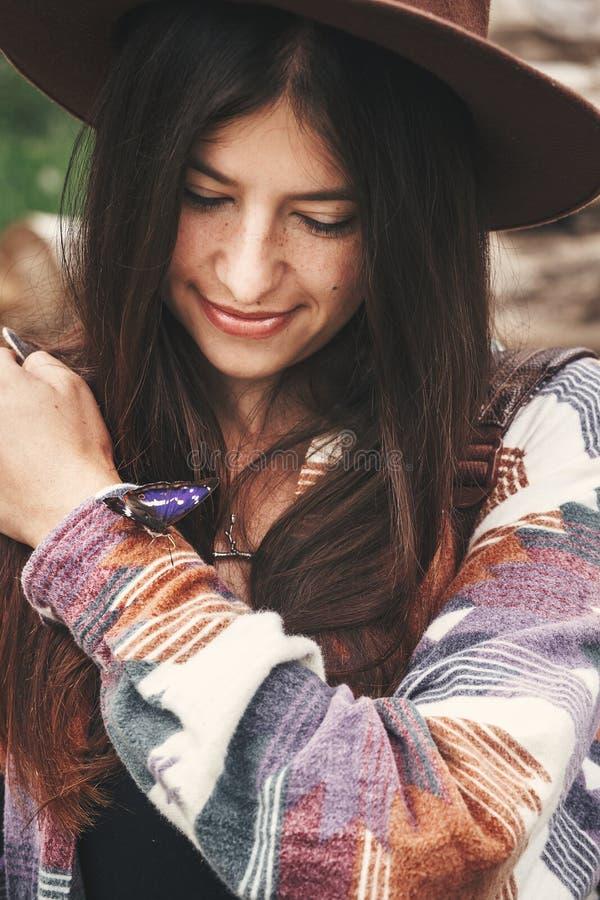 Stilfull hipsterflicka i hatten som förestående rymmer fjärilen för purpurfärgad kejsare i sommarberg Handelsresande för ung kvin fotografering för bildbyråer