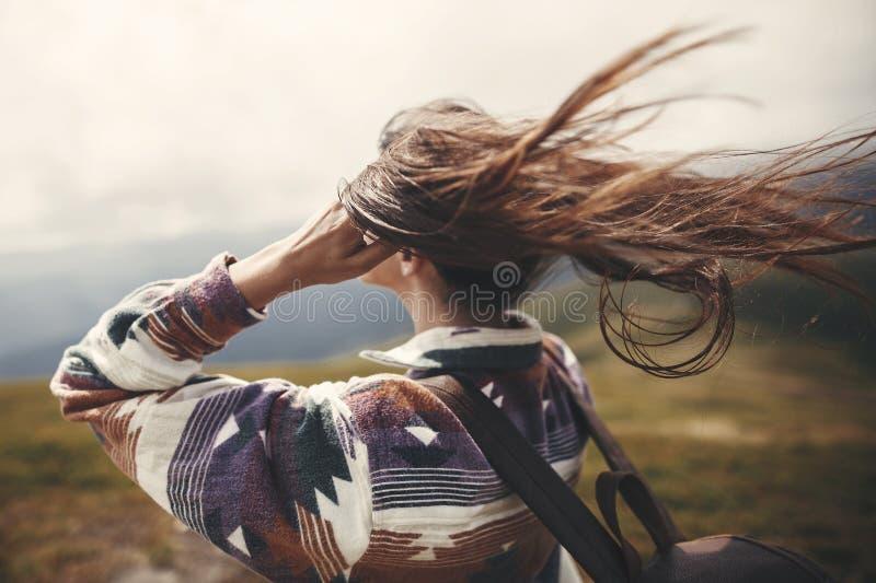 Stilfull hipsterflicka med ryggsäcken och blåsigt hår överst av berg Stående av lyckligt koppla av för ung kvinna carefree mood arkivfoto