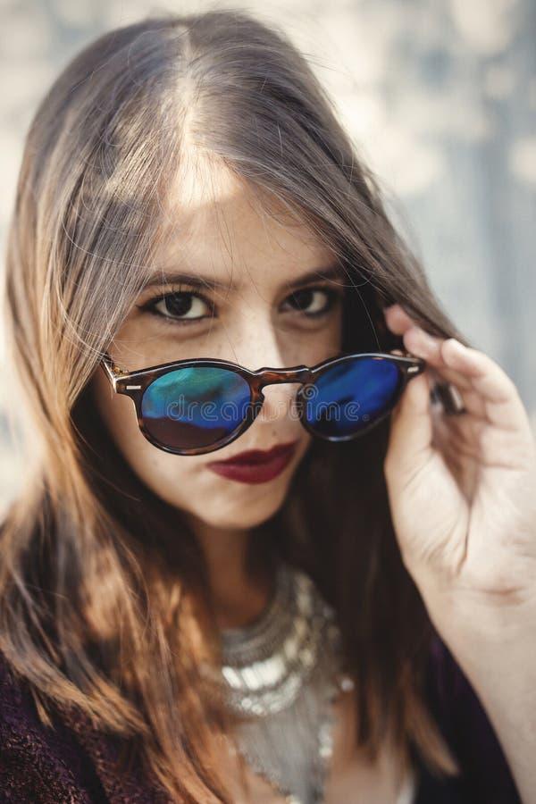 Stilfull hipsterflicka som ler i solig gata på bakgrund av träväggen Stående av bohoflickan i kall dräkt och solglasögon royaltyfria bilder