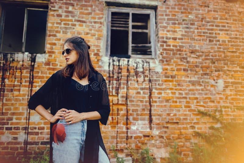 Stilfull hipsterflicka som poserar i gatan, atmosfäriskt ögonblick Trendig kall kvinna i svart solglasögon och grov bomullstvillj arkivbild