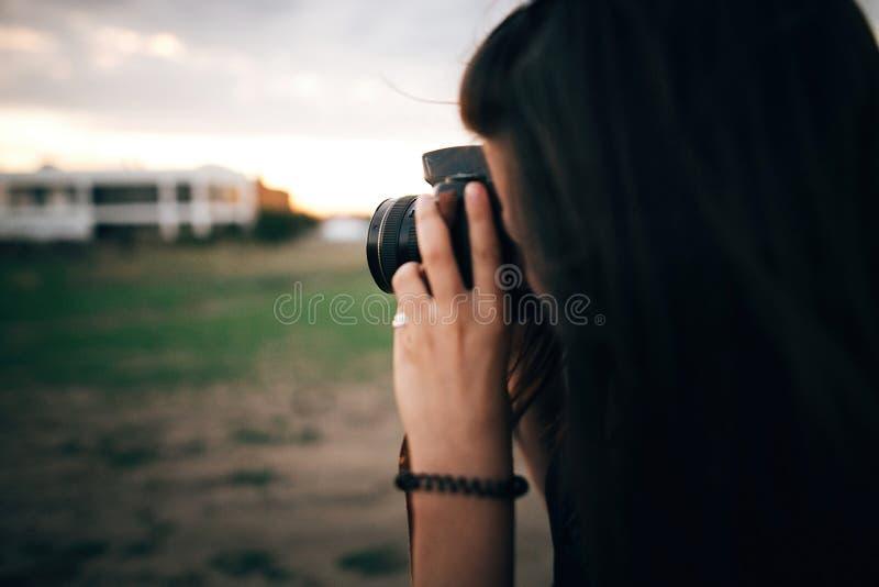 Stilfull hipsterflicka som tar foto p? stranden p? solnedg?ngen f?r sommarterritorium f?r katya krasnodar semester St?ende av den royaltyfria foton