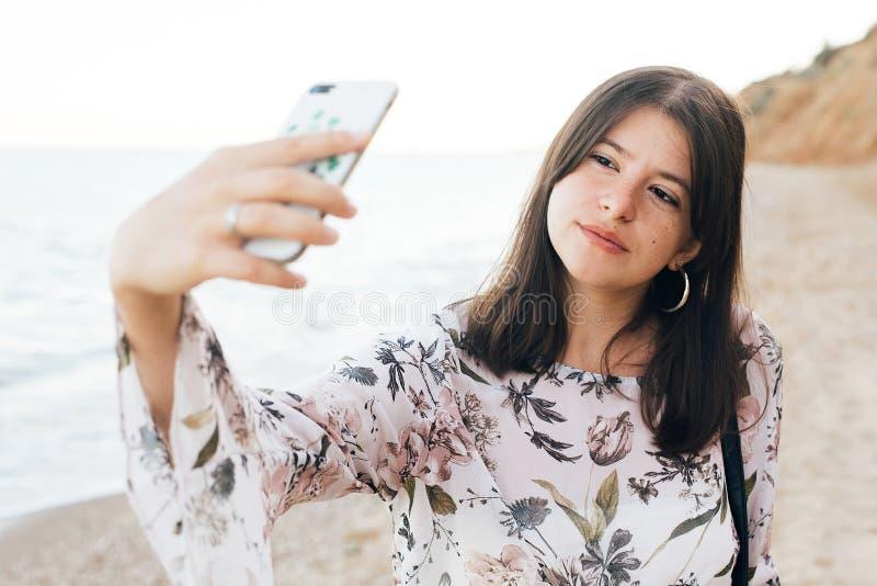 Stilfull hipsterflicka som tar selfie på telefonen på stranden och klippan nära havet f?r sommarterritorium f?r katya krasnodar s royaltyfri fotografi