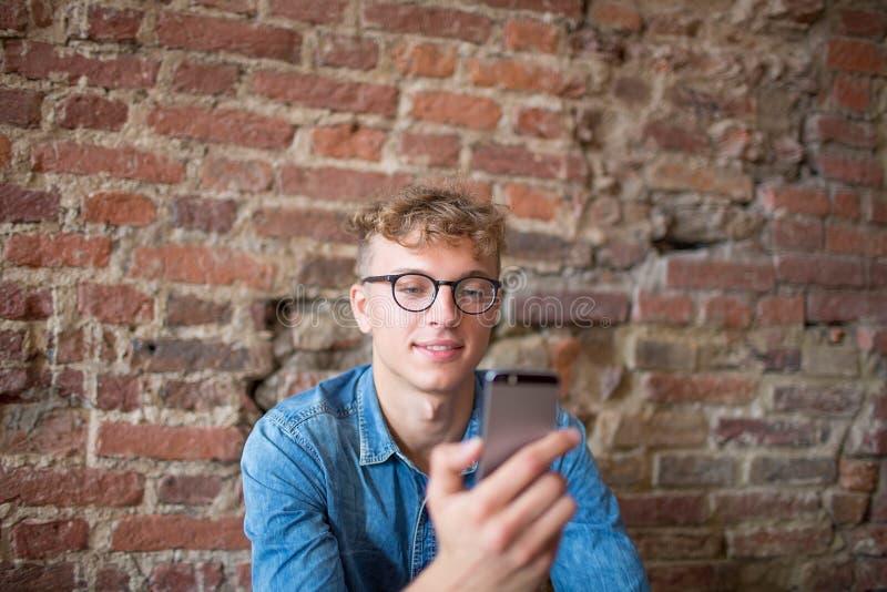 Stilfull hipstergrabb i exponeringsglas som läser textmeddelandet i internet på den moderna mobiltelefonen royaltyfri fotografi