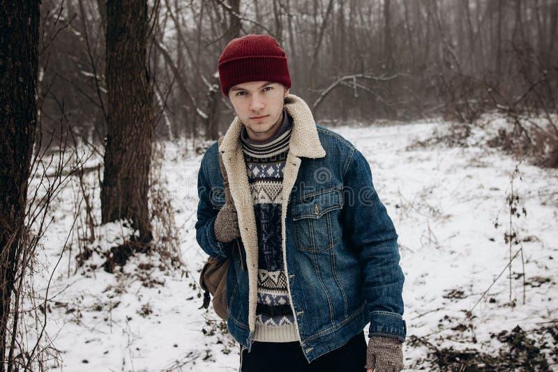 Stilfull hipsterhandelsresande med ryggsäcken som poserar i vintern snöig fo fotografering för bildbyråer