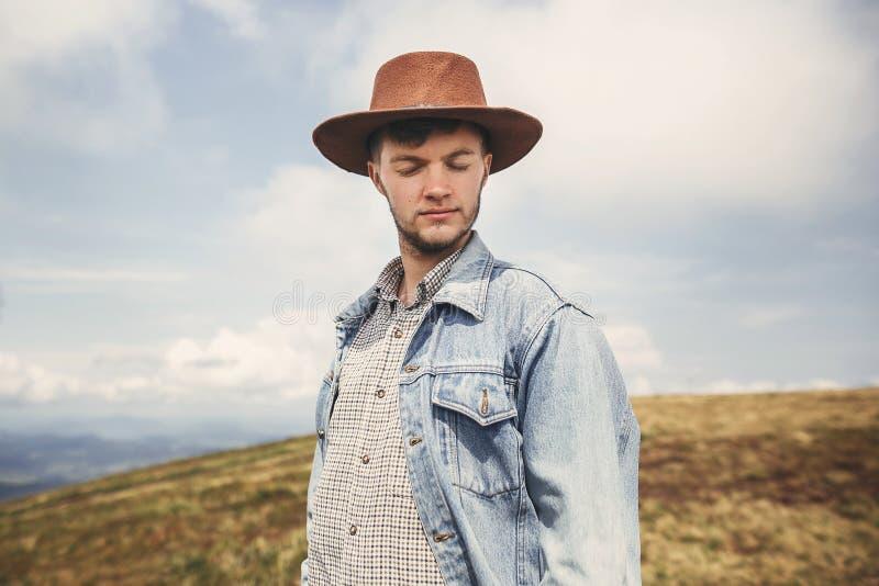 Stilfull hipsterhandelsresande som överst kopplar av av soliga kullar på bakgrund av berg kopiera avstånd Stilig man i hatt som i royaltyfri foto