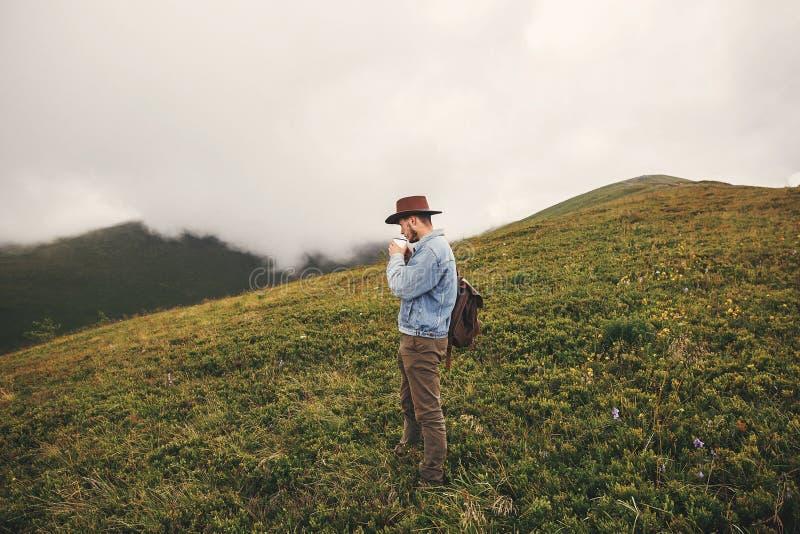 Stilfull hipsterhandelsresande som dricker te och överst står av kullar på bakgrund av dimmiga berg kopiera avstånd Stilig man in arkivbild