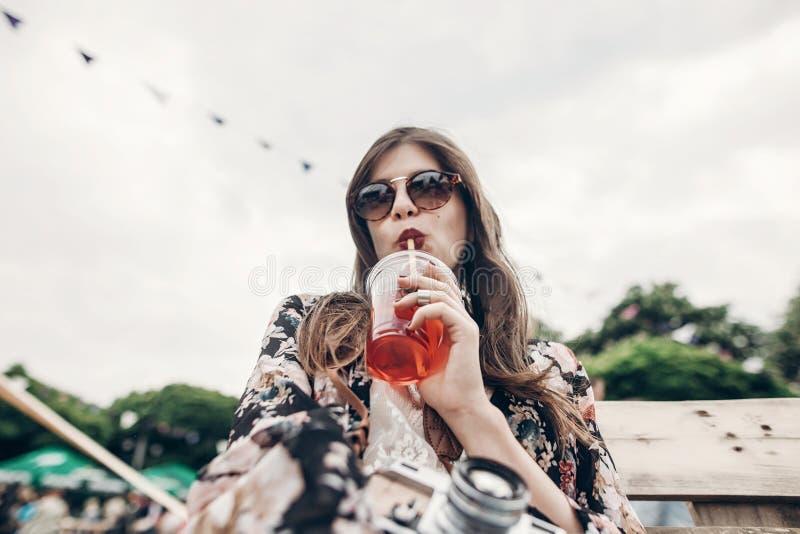 stilfull hipsterkvinna som dricker lemonad kall bohoflicka i grov bomullstvill arkivfoton
