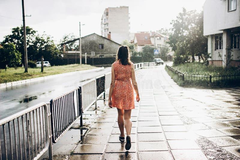 Stilfull hipsterkvinna som går i solig regnig gata i sommarFN royaltyfria foton
