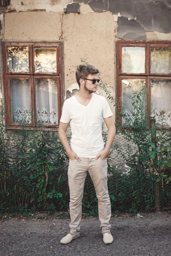 Stilfull hipsterman i solglasögon som utomhus poserar i solig bygd på det gamla lantliga huset Stilig skäggig man som in kopplar  royaltyfri foto