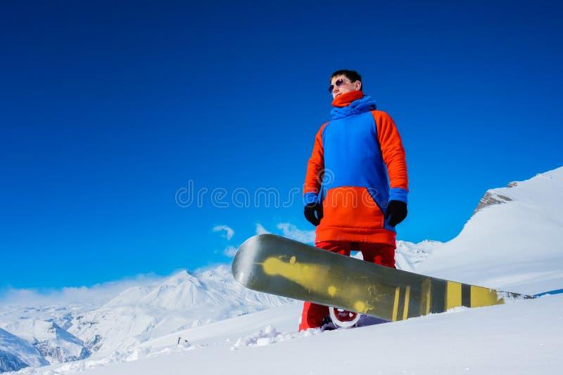 Stilfull idrottsman nensnowboarder mot bakgrunden av snöberg royaltyfri bild