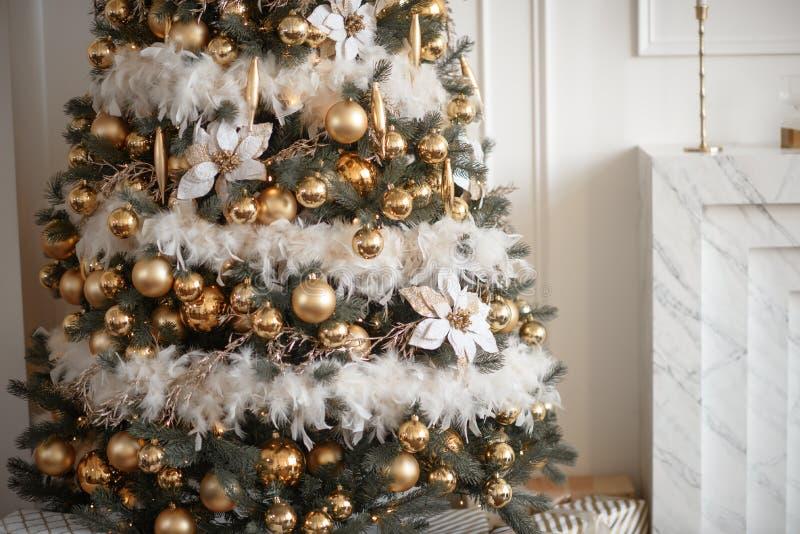 Stilfull julvardagsrumdekor i guld- och silversignaler Stora beautifully dekorerade ställningar för en julgran i det nästa rummet royaltyfria bilder