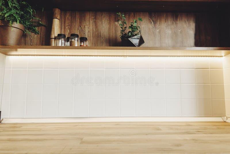 Stilfull kökinredesign Lyxigt modernt kökmöblemang i grå färg och trätabletop Utrymme för text Hylla med arkivfoton