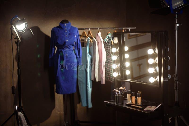 Stilfull kläder och sminkprodukter i loge arkivbild