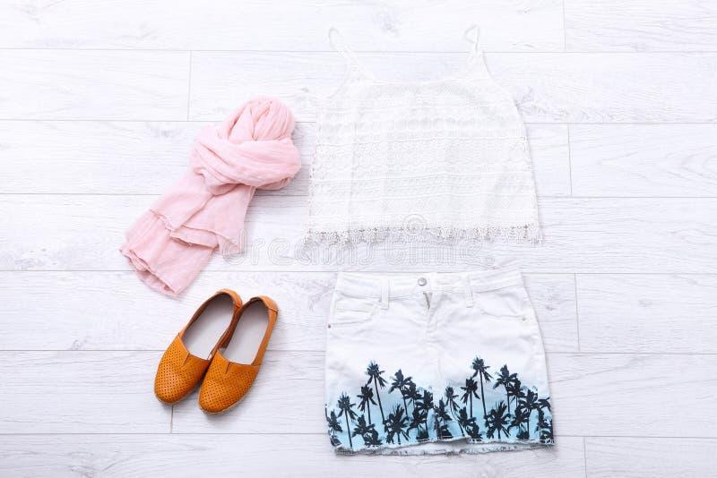 Stilfull kläder och tillbehör på det vita trägolvet Top beskådar royaltyfria bilder