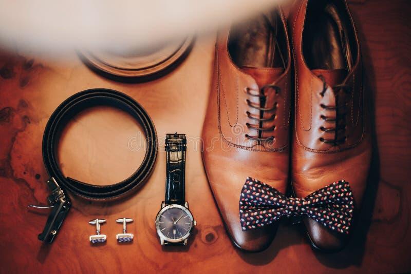 Stilfull klocka, dyrt, skor, fluga, cufflinks och bälte för brudgum på trätabellen i hotellrum Morgonförberedelse för fotografering för bildbyråer