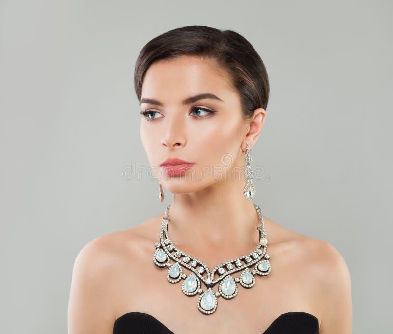 Stilfull kvinna med kort hår, makeup och diamantsmycken, modestående royaltyfri foto