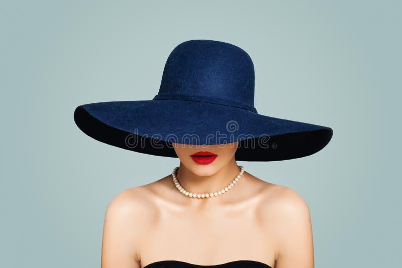 Stilfull kvinna med röd kantmakeup som bär den klassiska hatten och vita pärlor, modestående arkivfoton