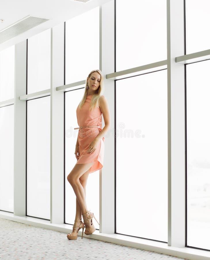 Stilfull kvinna nära fönster i kontorsbyggnaden royaltyfri fotografi