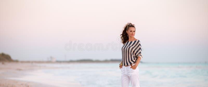 Stilfull kvinna på stranden i afton royaltyfri fotografi
