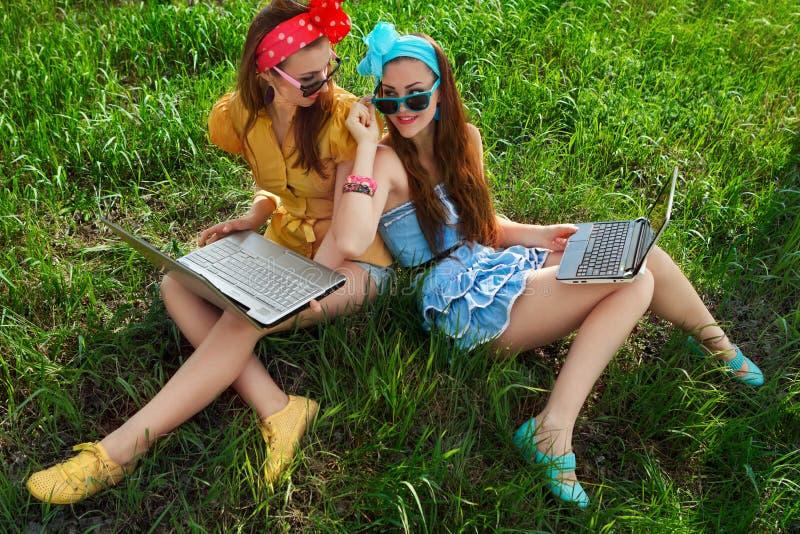 Stilfull kvinna som använder bärbara datorer royaltyfri foto
