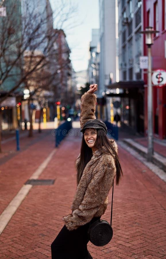 Stilfull kvinna som lyfter upp händer för positiv känsla och celebrat arkivfoton