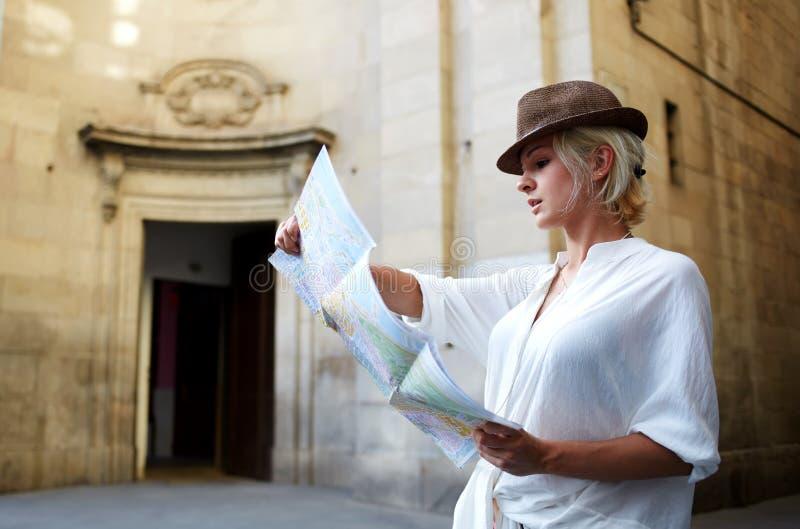 Stilfull kvinna som på söker översikten vägen till något, medan stå nära den arkitektoniska monumentet utomhus arkivfoton