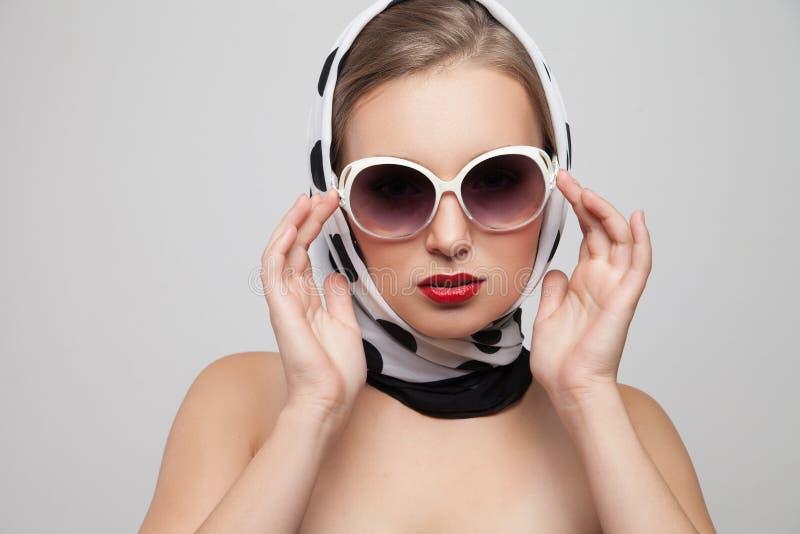 Stilfull kvinna som poserar i solglasögon och halsduk på royaltyfri foto