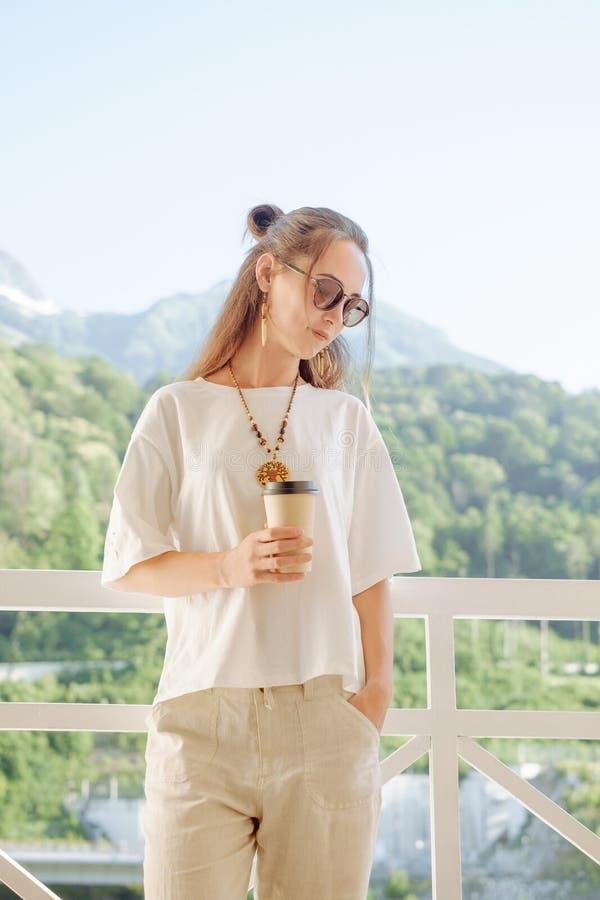 Stilfull kvinna som vilar med koppen kaffe p? balkong arkivfoto