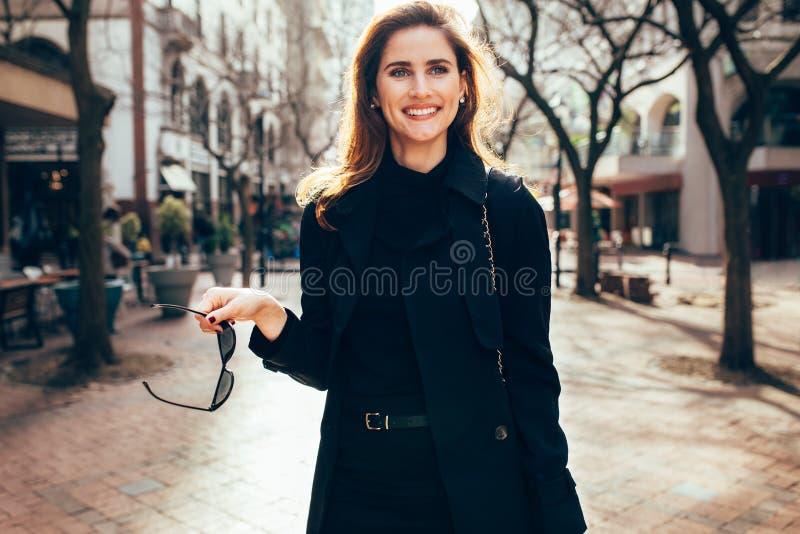 Stilfull kvinnlig med solglasögon som går på stadsgatan royaltyfria foton