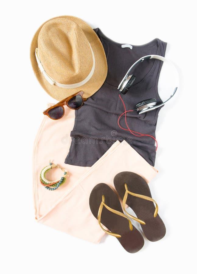 Stilfull kvinnligkläderuppsättning Sommarkvinna/flickadräkt på vit bakgrund Persikakjol, brun behållare, sugrörhatt, hörlurar, fl royaltyfri foto