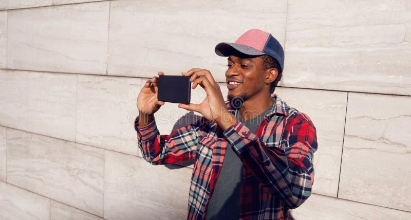 Stilfull le afrikansk man som tar selfiebilden vid telefonen i baseballmössan, plädskjorta på stadsgatan över den gråa väggen arkivfoton