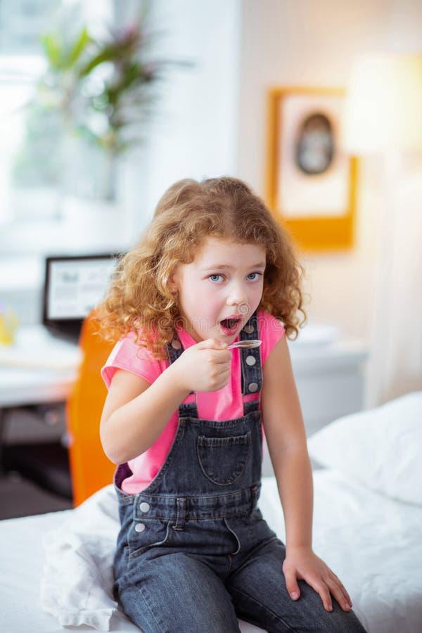 Stilfull liten flicka som sitter i sjukhuset och tar hostasirap fotografering för bildbyråer