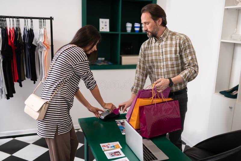 Stilfull lockande brunett som gör betalning vid en kreditkort fotografering för bildbyråer