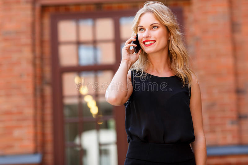 Stilfull lycklig blond kvinna som talar på telefonen och att le arkivbild
