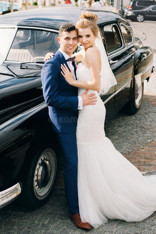 Stilfull lycklig brud och brudgum som poserar på den gamla retro bilen Ursnygga brölloppar av nygifta personer som ler och kramar royaltyfria bilder