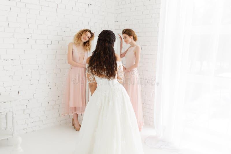 Stilfull lycklig bruddressing i klänningen som ler till brudtärnor, på spegeln, lantlig bröllopmorgonförberedelse _ arkivfoton