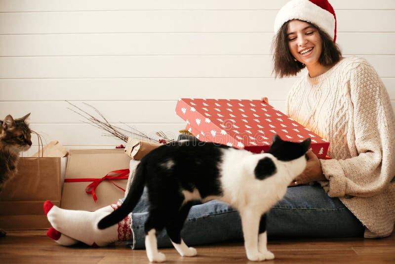 Stilfull lycklig flicka, i den santa hatten och för julgåva för hemtrevlig tröja öppnande ask och att spela med katter i dekorera royaltyfria bilder