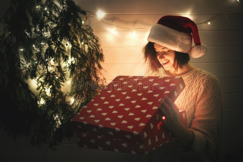 Stilfull lycklig flicka i den santa hatten och för julgåva för hemtrevlig tröja öppnande ask med magiskt ljus i mörkt rum på det  arkivfoton
