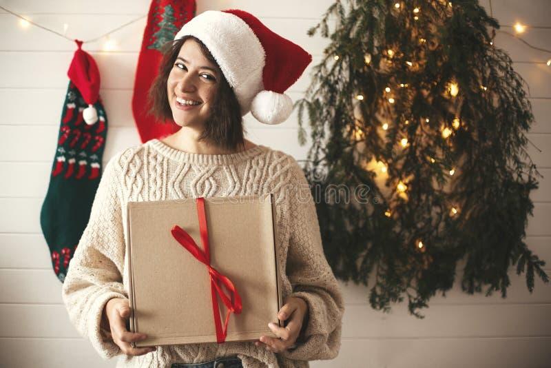 Stilfull lycklig flicka i den santa hatten som rymmer julgåvaasken på bakgrund av det moderna julträdet, ljus och strumpor Barn arkivbild