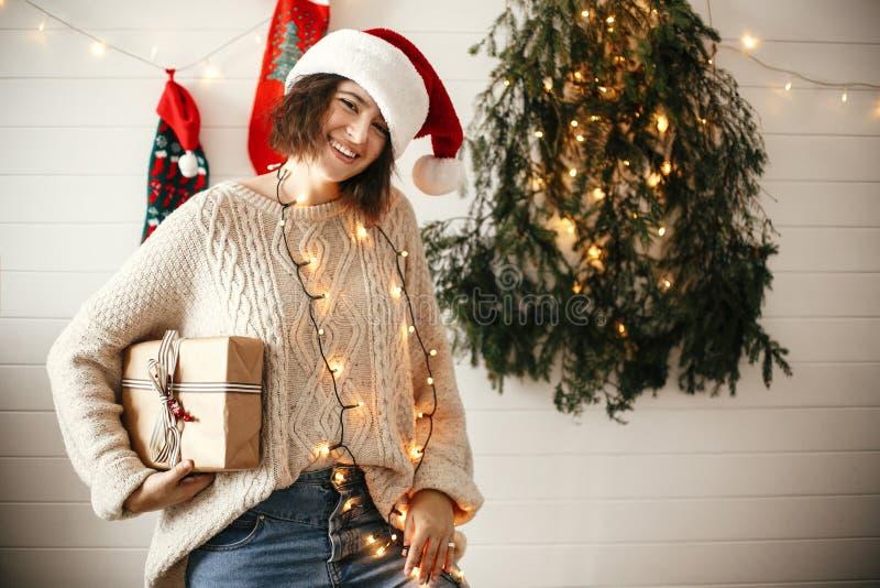 Stilfull lycklig flicka i den santa hatten som rymmer julgåvaasken på bakgrund av det moderna julträdet, ljus och strumpor Barn royaltyfria foton