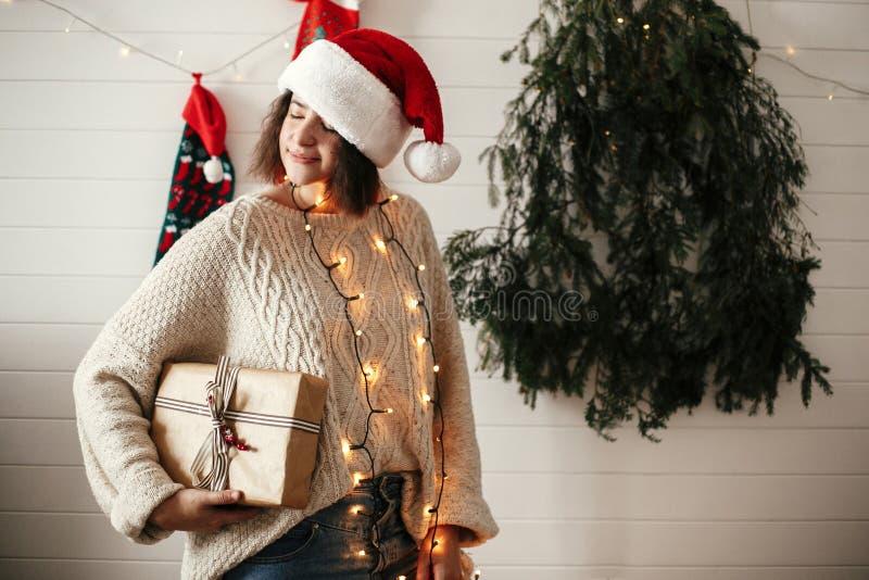 Stilfull lycklig flicka i den santa hatten som rymmer julgåvaasken på bakgrund av det moderna julträdet, ljus och strumpor Barn royaltyfri bild