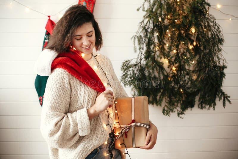 Stilfull lycklig flicka med den santa hatten som rymmer julgåvaasken på bakgrund av det moderna julträdet, ljus och strumpor Barn royaltyfria bilder
