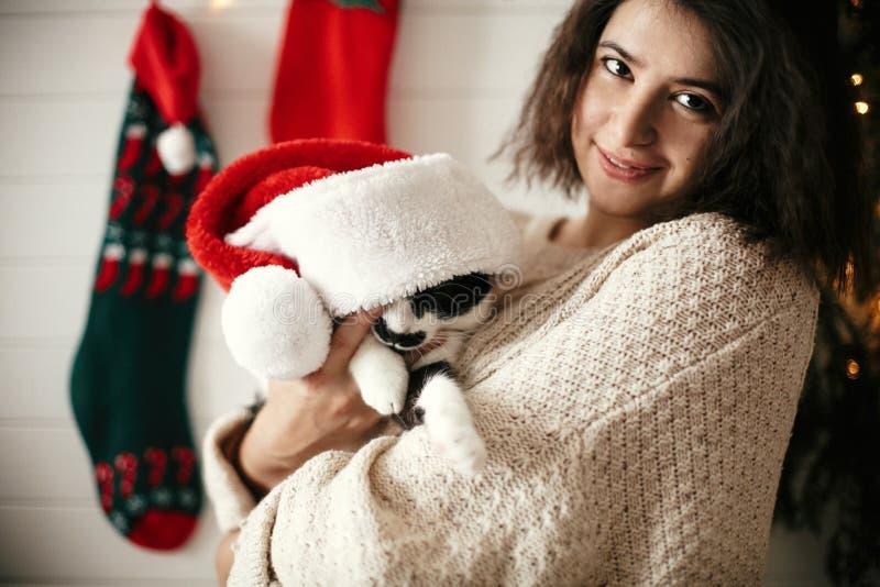 Stilfull lycklig flicka som ler och spelar med den gulliga katten i den santa hatten i bakgrund av ljus och strumpor för julträd  arkivbild