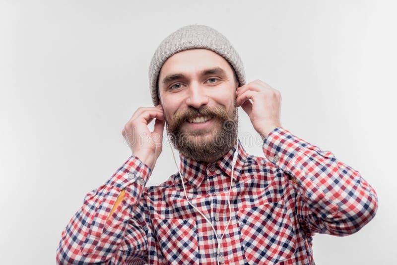 Stilfull mörkhårig man som använder hörluren, medan lyssna till musik royaltyfria foton