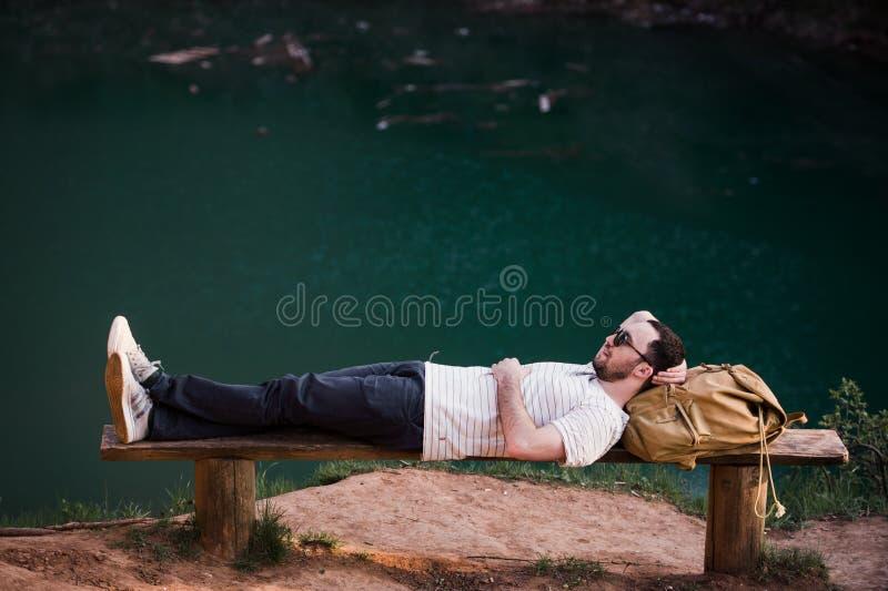 Stilfull man för fotvandrare som ligger på en träbänk nära sjön fotografering för bildbyråer
