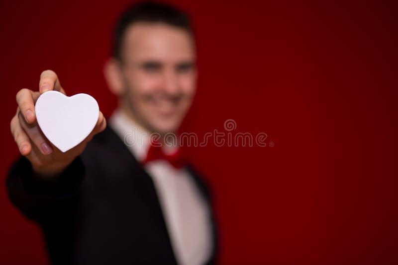 Stilfull man i ask för gåva för dräktinnehavförälskelse med röd bakgrund, fokus på gåvaasken royaltyfri bild