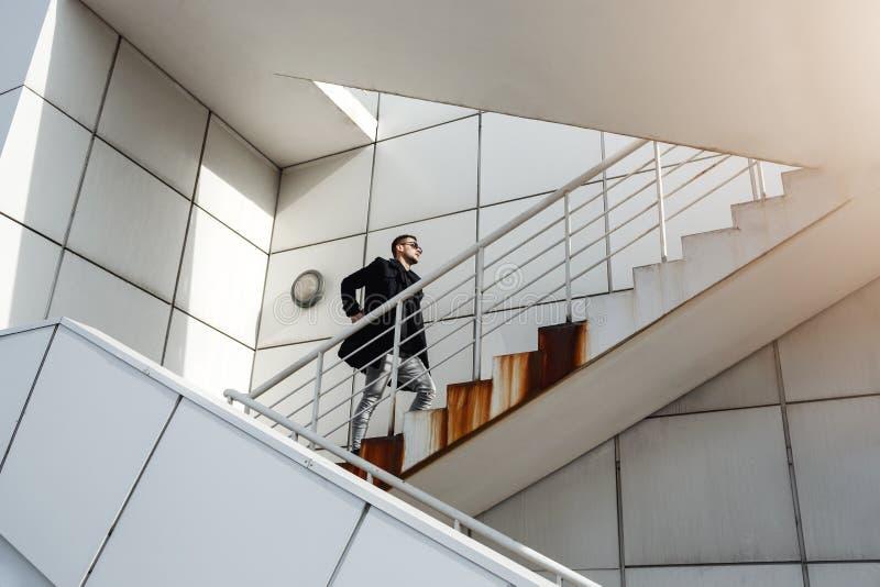 Stilfull man i det tillbaka laget som uppför trappan går Minimalizm stil arkivbilder