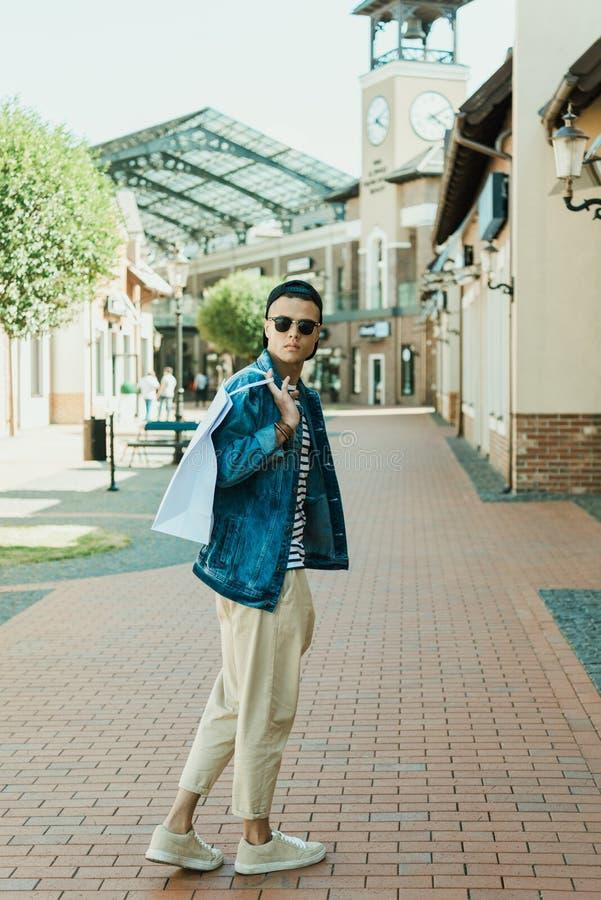 Stilfull man i solglasögon som rymmer shoppingpåsen och anseende på gatan arkivfoto