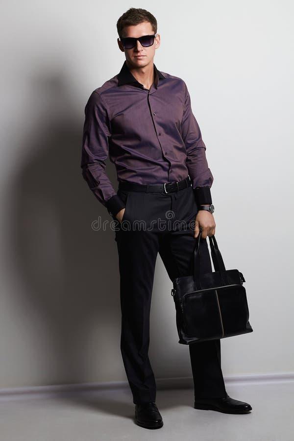 Stilfull man med en handväska mäktig look royaltyfri foto