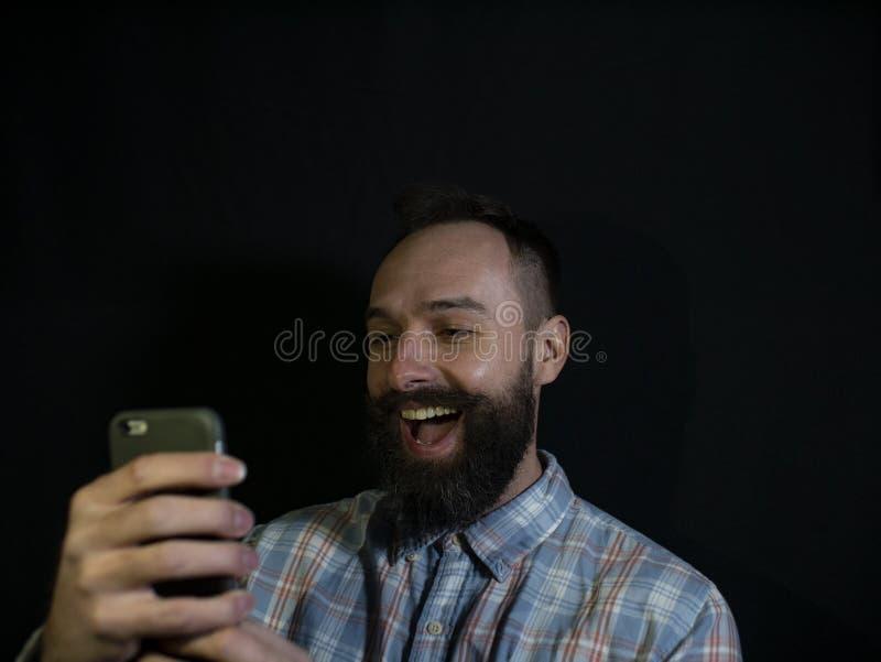 Stilfull man med ett skägg och mustaschblickar in i en mobiltelefon med en skratta framsida på en svart bakgrund royaltyfria foton